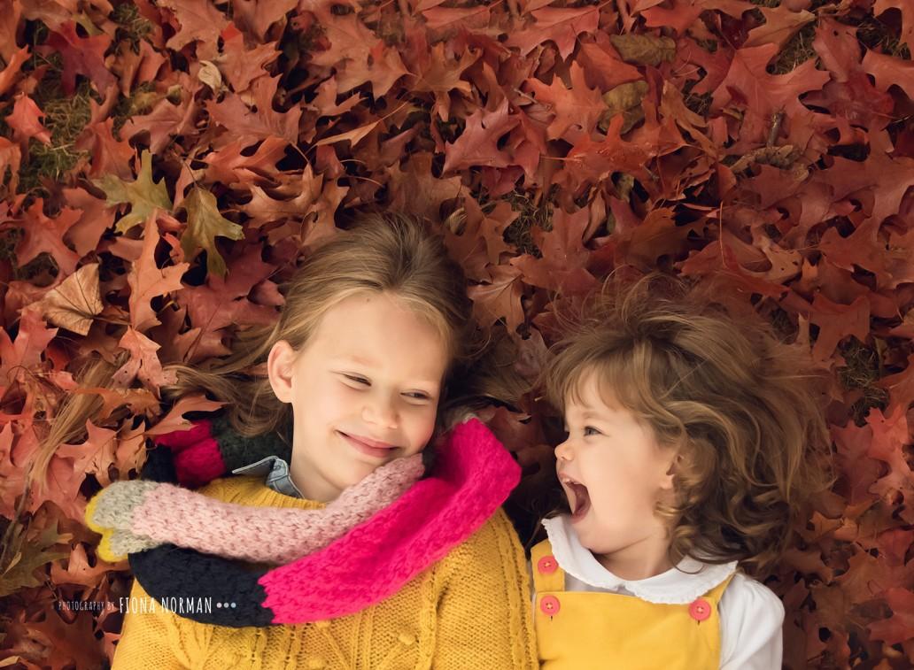 sisters laughing in leaves