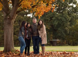 family photographed smiling under tree