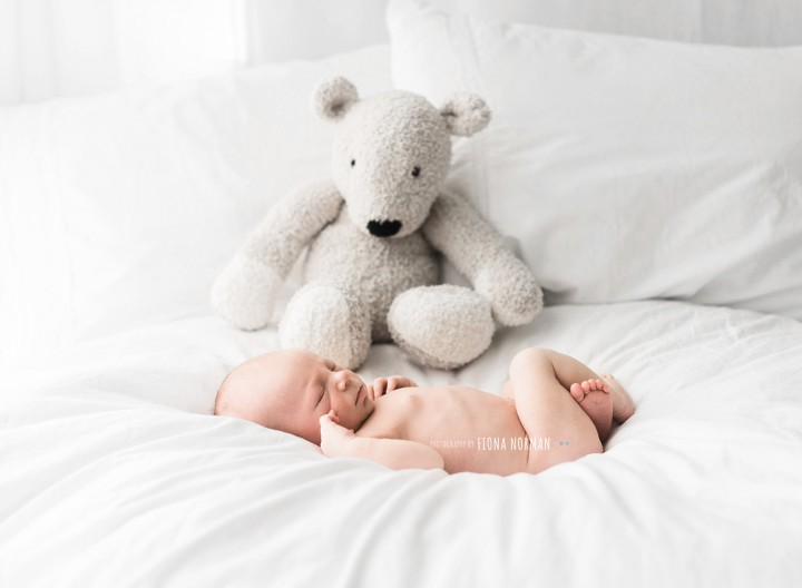 newborn baby on bed with teddy