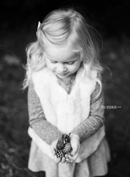 little girl with pinecones