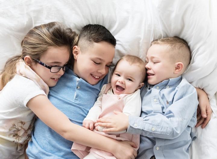 4 siblings lying on bed