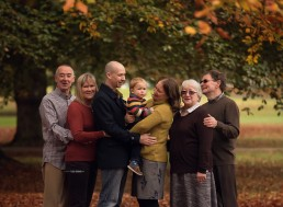 family standing in autumn leaves